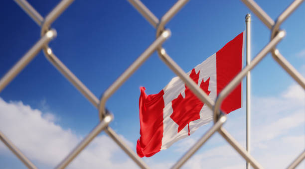 Fence In Front Of Canadian Flag Fence in front of Canadian flag. Illegal immigration concept. Horizontal composition with copy space. deportation stock pictures, royalty-free photos & images