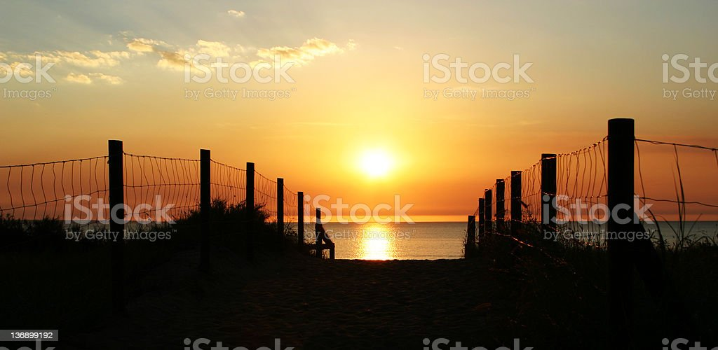 Fence line making a pathway to the sea captured in sunset stock photo