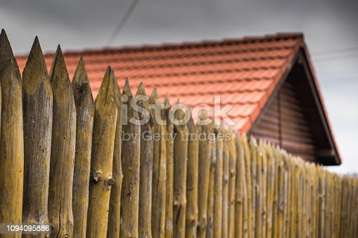 A fence made of sharp wooden stakes against the background of a wooden house with a red tiled roof and a gray sky.