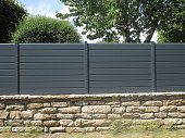 PVC fence mounted on a stone wall