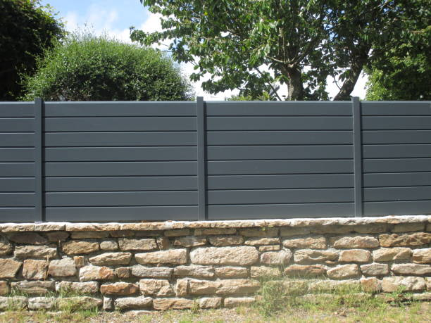 Cтоковое фото PVC fence mounted on a stone wall