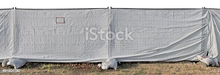 istock A fence of constrution site made of metal mesh and a white  synthetic canvas. 891904190
