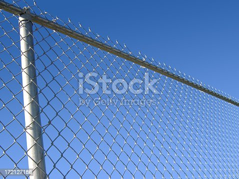 Cold steel chain-link fence with vivid blue sky behind.