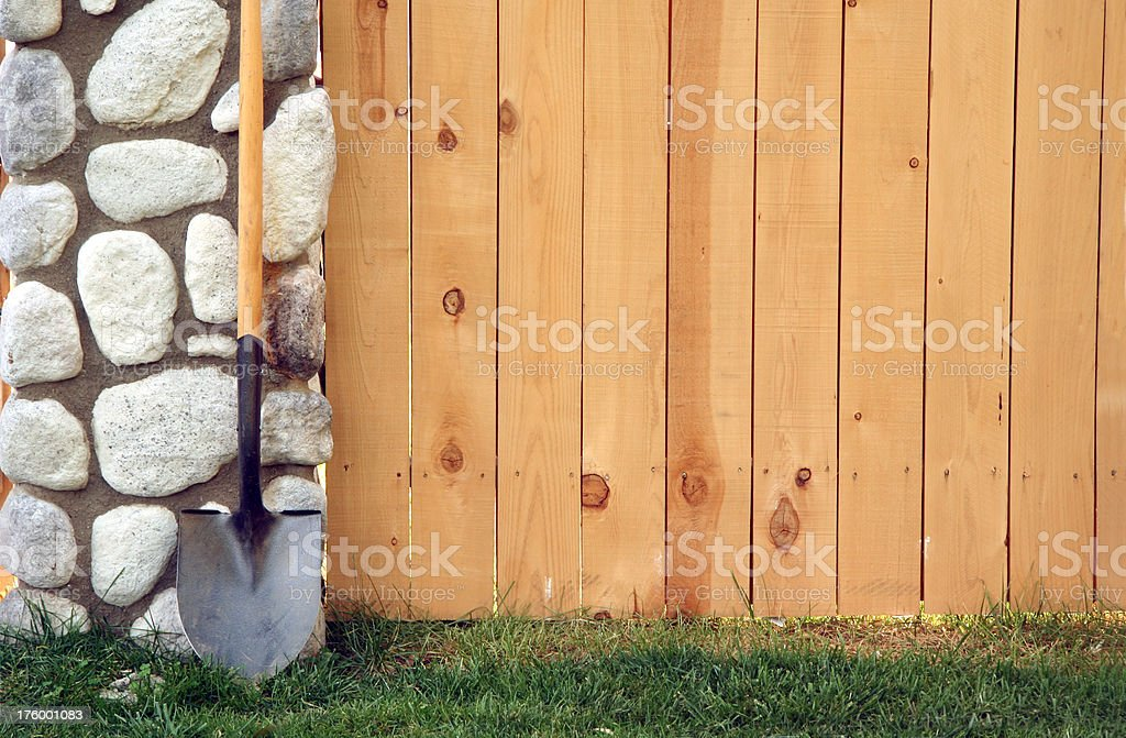 Fence, Stone Column, and Shovel royalty-free stock photo