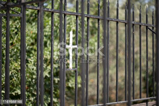 Detail (close-up) of iron fence surrounding a cemetery with small chapel on the Greek Island of Chios at midday in summer. Shallow depth of field. Blurred background. The image was captured with a prime lens and a full frame DSLR camera at low ISO resulting in large clean files.