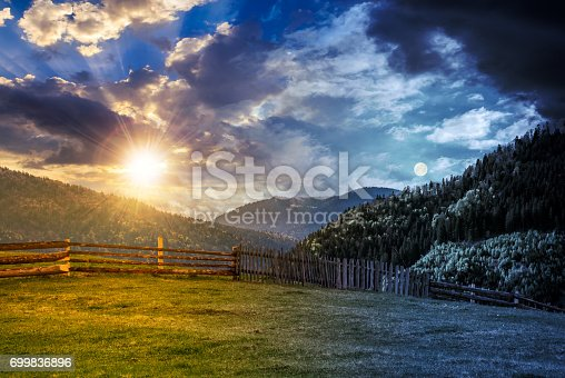 1074120624 istock photo fence through the grassy meadow in mountains time change concept 699836896
