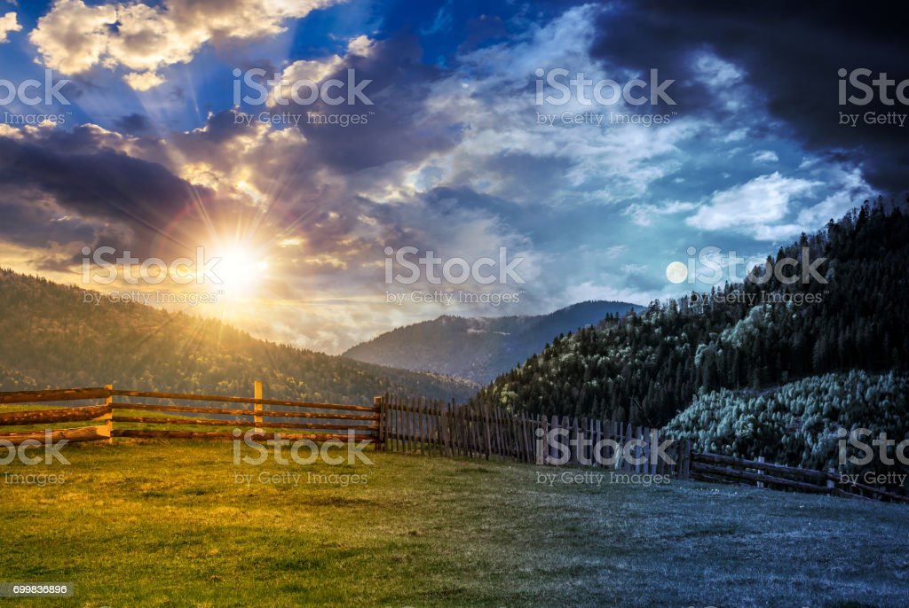 fence through the grassy meadow in mountains time change concept stock photo