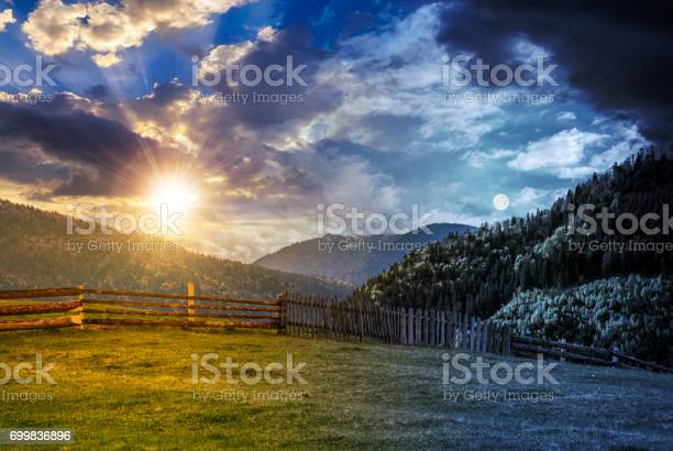 Photo of fence through the grassy meadow in mountains time change concept