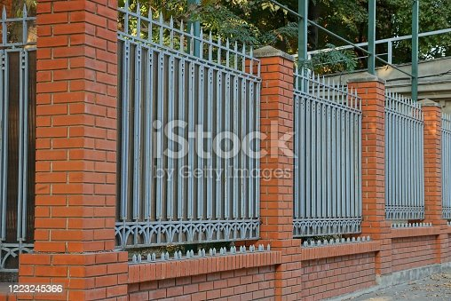 istock fence wall of red bricks and gray metal with sharp bars 1223245366