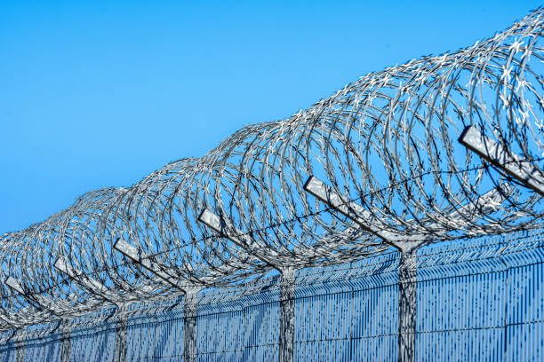 fence with barbed wire against blue sky with clouds fence with barbed wire against blue sky with clouds, security concept frontier field stock pictures, royalty-free photos & images