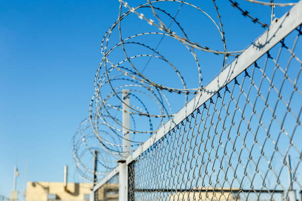 fence with barbed wire fence with barbed wire, barbed wire on a wire mesh fence antiterrorist stock pictures, royalty-free photos & images