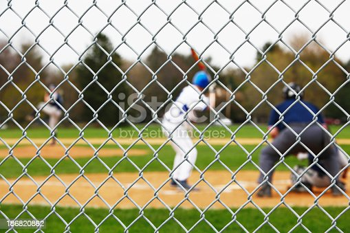 Beyond a sturdy protective chainlink fence safety backstop, a baseball pitcher is winding up to pitch to a waiting batter, catcher and umpire during a high school baseball game. Selective focus on the fence - with the players and umpire intentionally blurred.