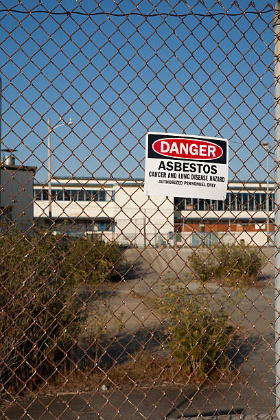 fence with danger asbestos warning sign attached to it. - bioremediation stock photos and pictures