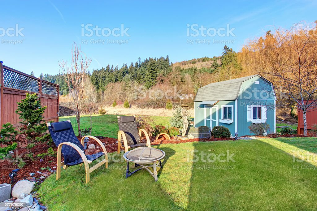 Fenced back yard with blue barn shed. stock photo