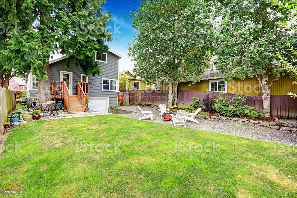 Fenced back yard with patio area and white adirondack chairs. stock photo