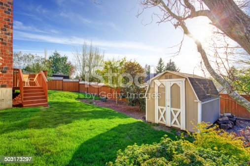 Fenced backyard with wooden walkout deck and small shed