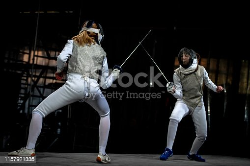 Fencer female athletes fighting against black background during the Olympics.
