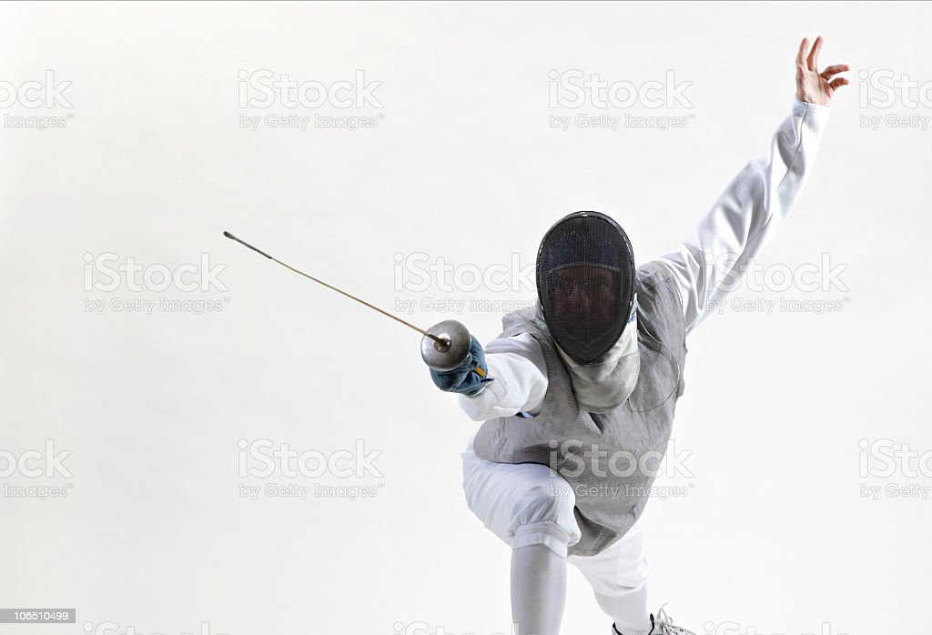 A fencer in attack position against white background royalty-free stock photo