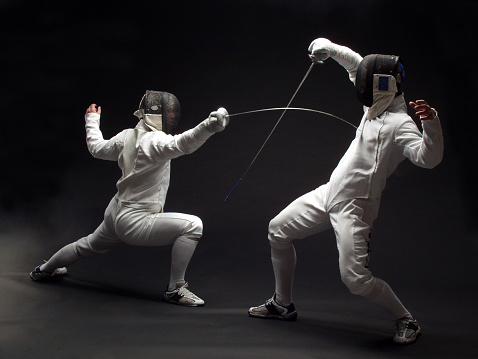 two fencers in action on black background