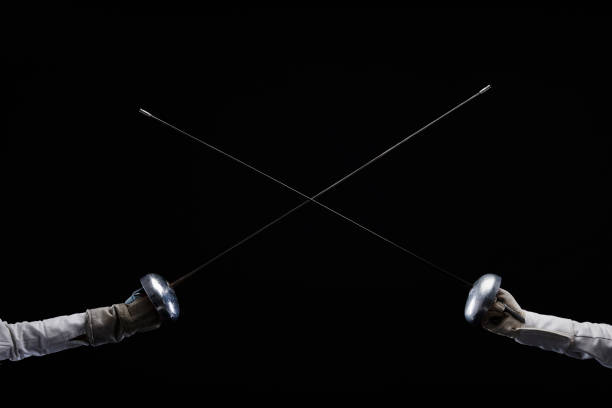Fencing swords crossed. Close-up shot. Épée and Sabre type of fencing weapon. Dark black background. Fencing sport competition Duel stock photo