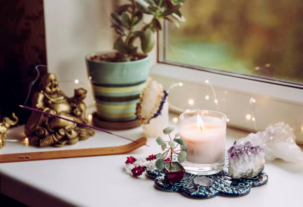 feng shui altar zu hause im wohnzimmer oder schlafzimmer. anziehung von wohlstand s anziehungskraft und wohlstandskonzept. kristallhaufen, drahtbaum mit edelsteinen, golden lächelnde buddha-figur auf tischfensterbank. - altar stock-fotos und bilder