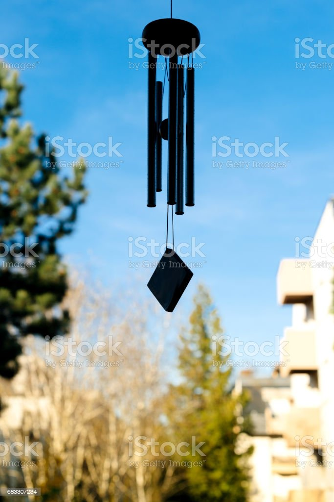 Feng shui chimes with blue sky and house nature in the background royalty free stockfoto