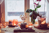 Feng Shui nature theme altar at home table and on window sill. Earth element( rock crystal clusters), wood element( wood discs), fire element( candles), rock salt candle holder. Positive home energy.