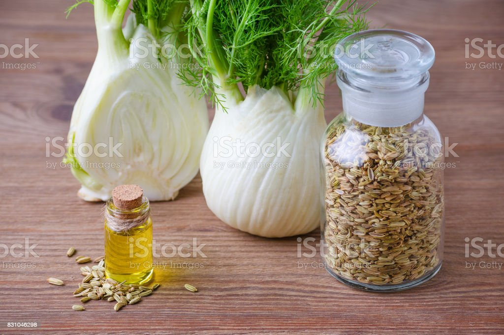 fennel essential oil, bulb and seeds, selective focus on dark wooden stock photo