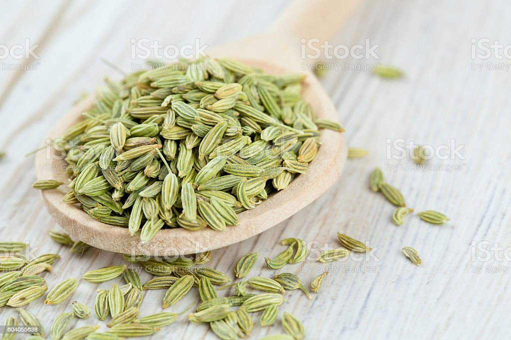 fennel seed in a wooden spoon on table stock photo