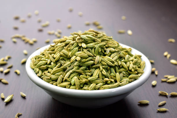 Fennel seeds in a bowl on a wooden table Fennel seeds in a bowl on a wooden table fennel stock pictures, royalty-free photos & images