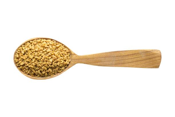 graines de fenugrec dans la cuillère de bois, isolée sur fond blanc. épices pour cuire les aliments, vue de dessus. - fenugrec photos et images de collection