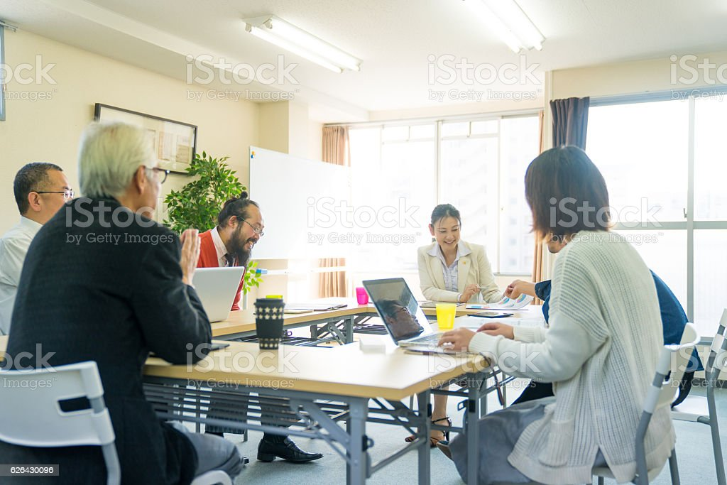 Fermale teacher with adult students in community college stock photo