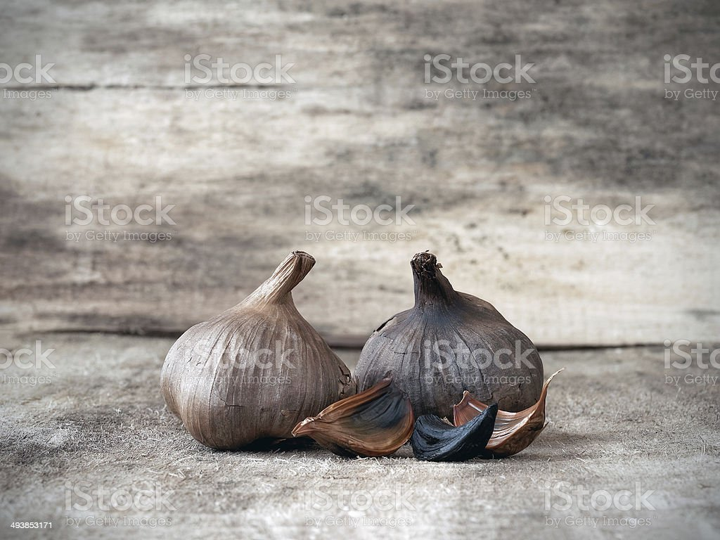 Fermented black garlic bulbs and cloves stock photo