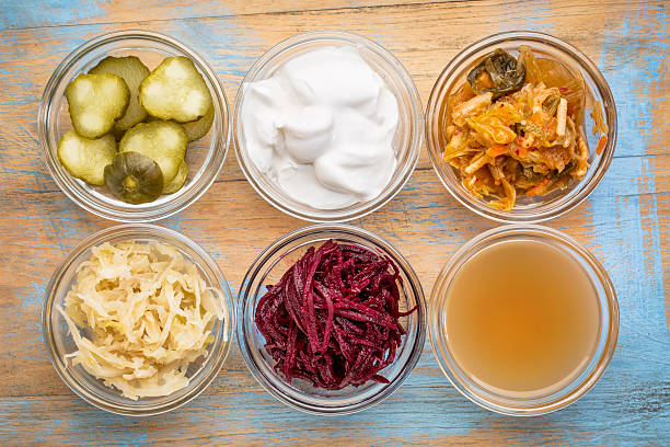 fermented food collection a set of fermented food great for gut health - top view of glass bowls against grunge wood:  cucumber pickles,  coconut milk yogurt, kimchi, sauerkraut, red beets, apple cider vinegar probiotic stock pictures, royalty-free photos & images