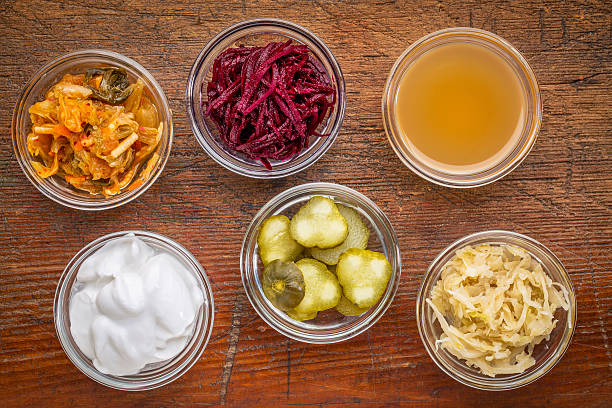 fermented food sampler a set of fermented food great for gut health - top view of glass bowls against wood:  kimchi, red beets, apple cider vinegar, coconut milk yogurt, cucumber pickles, sauerkraut fermenting stock pictures, royalty-free photos & images