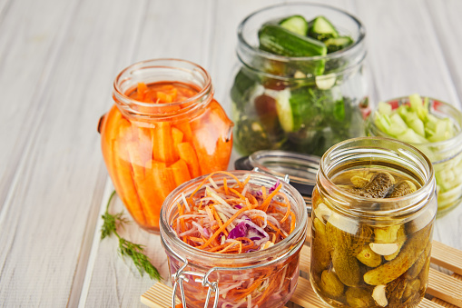 Fermented preserved vegetarian food concept. Sour sauerkraut, pickled carrots, pickled cucumbers, pickled celery in glass jars on a white wooden kitchen table. The concept of canned food. Copy space