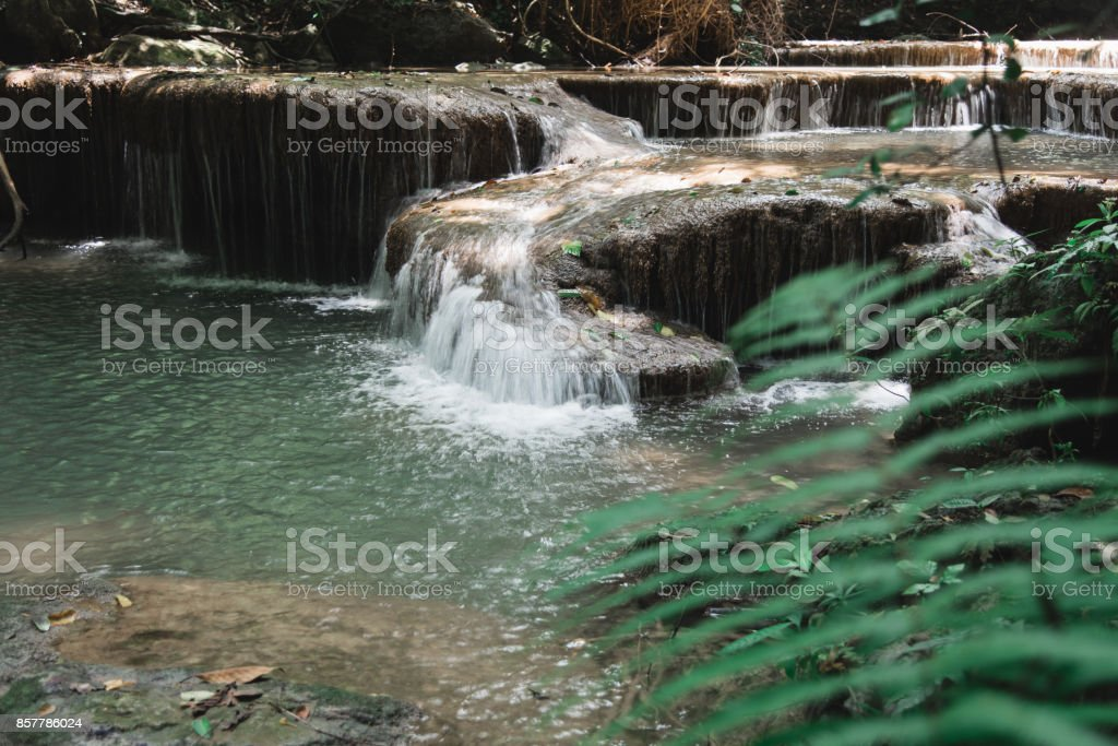 Fern and Waterfall at Erawan National Park, Thailand (focus on waterfall) stock photo