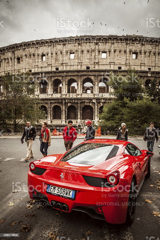 Ferrari 458 Italia and Coliseum, in Rome Rome, Italy - December 16, 2012: A red Ferrari 458 Italia parked just in front of the Coliseum in Rome, with people passing by and admiring the super expensive sport car Brand Name Stock Photo