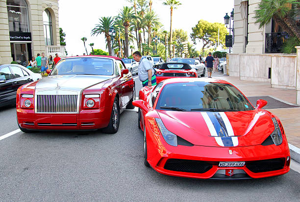 Ferrari 458 Italia Speciale Monte Carlo, Monaco - August 2, 2014: Red luxury car Rolls-Royce Drophead Coupe and supercar Ferrari 458 Italia Speciale parked at the city street near the casino. royce lake stock pictures, royalty-free photos & images