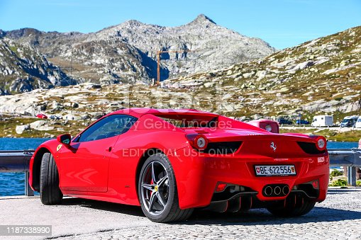 Saint Gotthard Pass, Switzerland - September 13, 2019: Red supercar Ferrari 458 Italia at the background of the Alps.