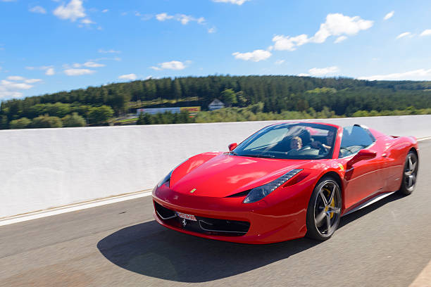 Ferrari 458 Spider sports car Spa, Belgium - September 27, 2015: Red Ferrari 458 Spider convertible sports car. The 458 Spider is the convertible version of the Ferrari 458 Italia V8 sports car. The car is driving around the race track during the 2015 Spa Italia event at the Spa Francorchamps race track.  ferrari stock pictures, royalty-free photos & images