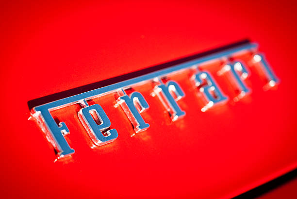 ferrari logo macro on red background with selective focus - badge logo stock photos and pictures