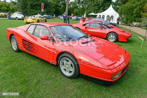 Red Ferrari Testarossa 1980s sports at a car show. The Testarossa (Type F110) is a 12-cylinder mid-engine sports car produced from 1984 to 1991. The car is on display during the 2017 Classic Days event at Schloss Dyck. People in the background are looking at the cars.