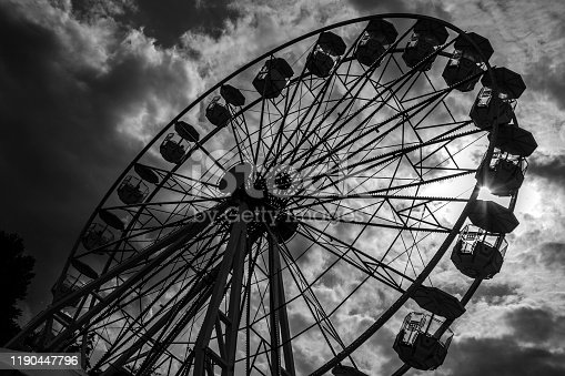 Black and white image of ferris wheel against stormy sky, Gdynia, Poland