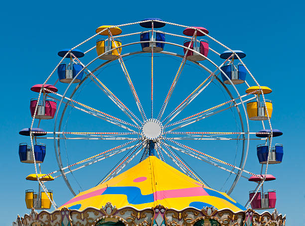 Ferris Wheel and Carousel Top Ferris Wheel and Carousel Top - colorful fair rides against blue sky ferris wheel stock pictures, royalty-free photos & images