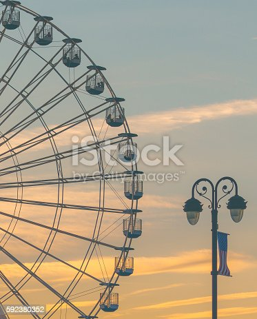 A Ferris Wheel with the sun setting behind it.