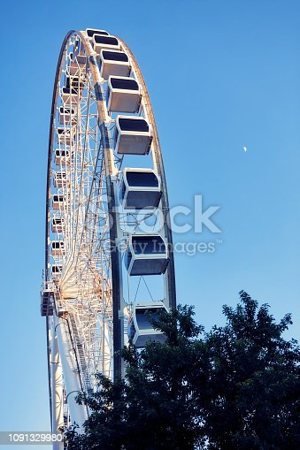 Ferris wheel and moon on a blue sky background at blue hour. Low angle vertical shoot.