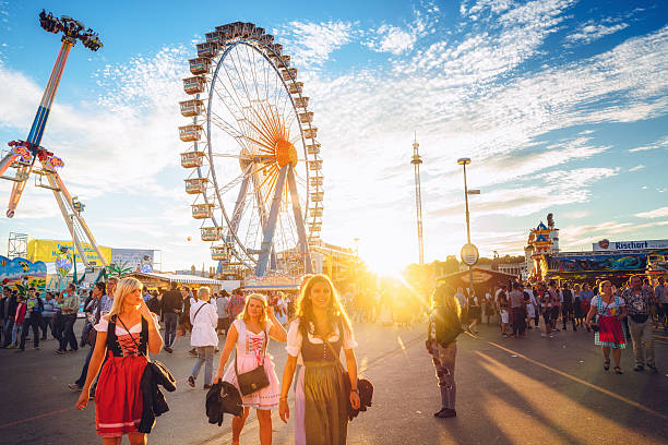 Ferris Wheel and Visitors Walking Through Oktoberfest Fairgrounds, Munich, Germany - Photo