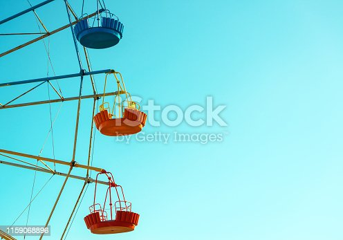 Ferris wheel cabins close-up on the blue sky background with copy space. Scenic view of detail of the colorful Ferris wheel in amusement park. Concept of holiday and children`s entertainment.
