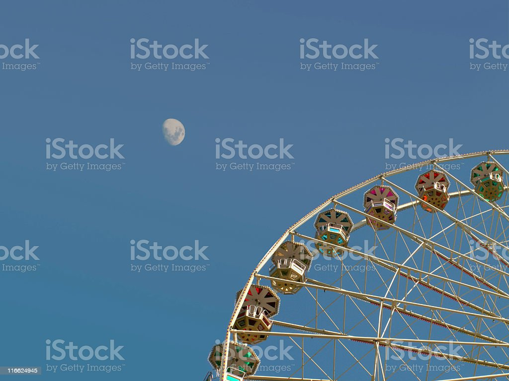Ferris wheel in front of the moon stock photo